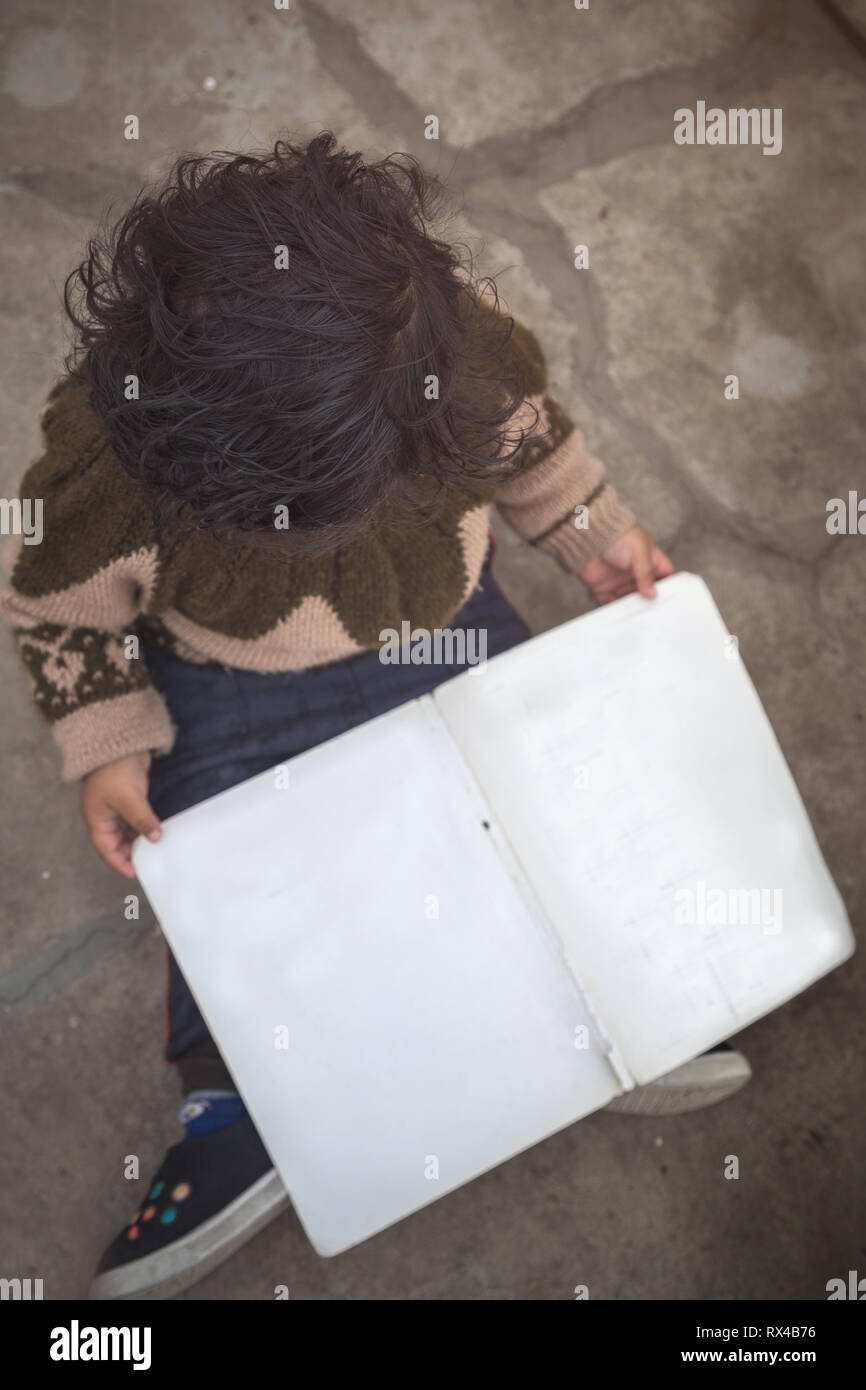 High angle view of Cute 2 year little Indian Asian baby girl kid with blank book while sitting on the floor. - Stock Image