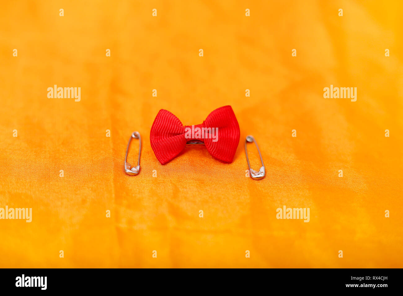 Portrait of safety pin and red bow. Isolated on the yellow background. Stock Photo