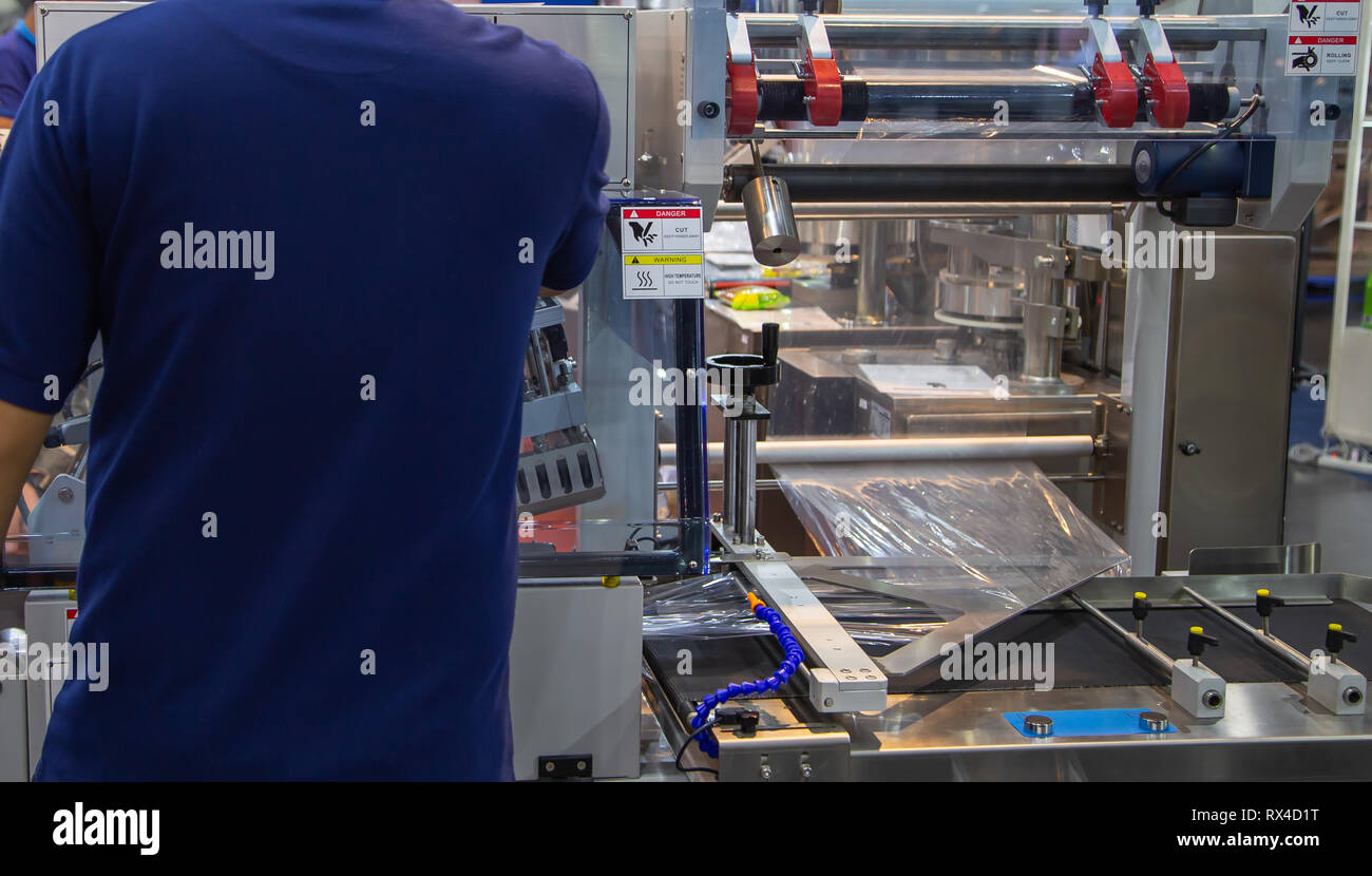 Industrial worker operate film wrapping packing machine - Stock Image