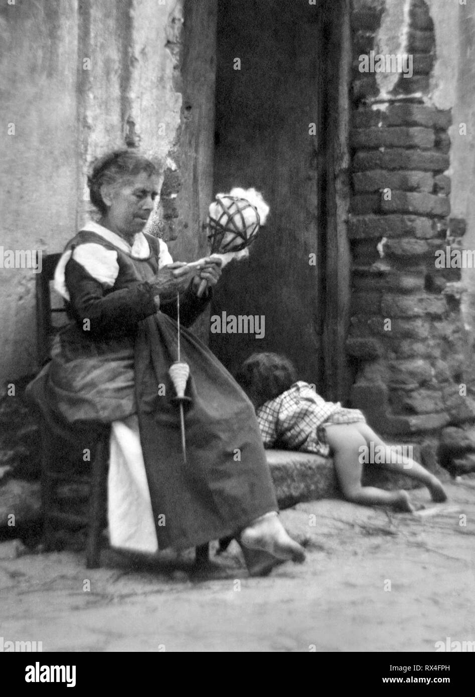 Europe, Italy, Calabria, Argusto, spinner of wool with child in front of house, 1940 - Stock Image