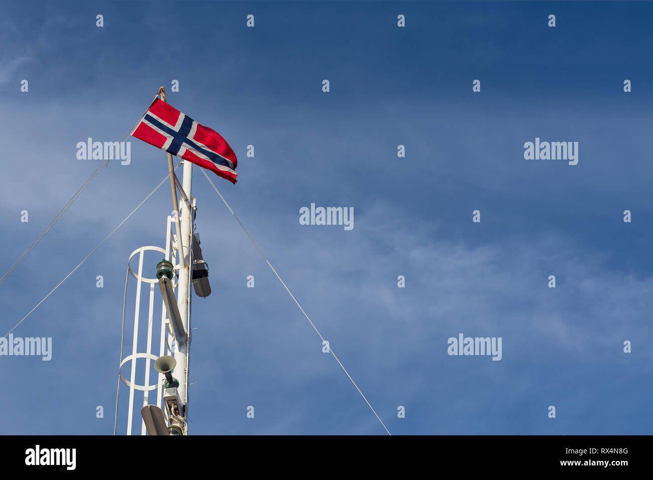 Norwegian flag on a flagpole against a blue sky. Sunny weather in Norway - Stock Image