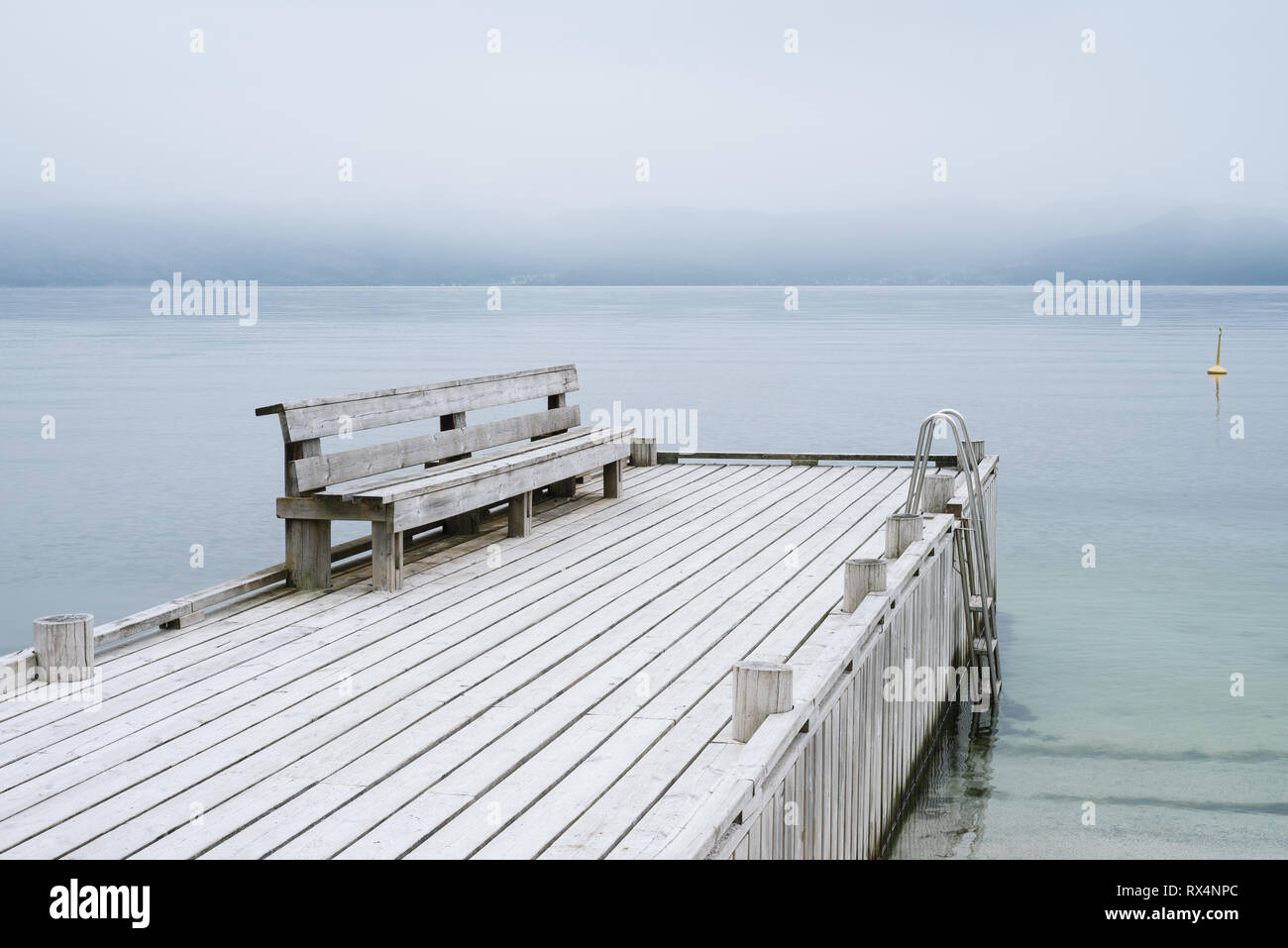 Norwegian landscape in gentle pastel colors. A wooden pier with a rest place. View of the Hardangerfjord Fjord. No far from the city of Oystese - Stock Image