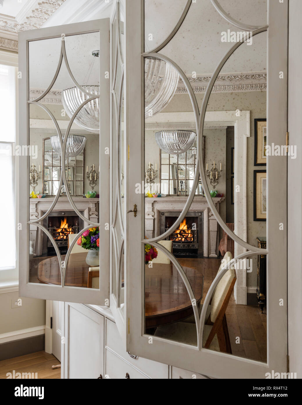 Reflection Of Dining Room In Mirrored Cupboard Stock Photo Alamy
