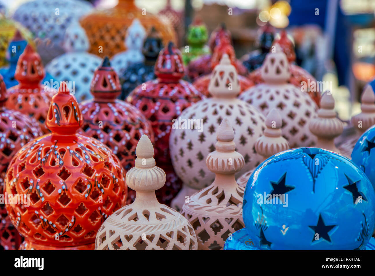 Background of colourful ceramic handicrafts with decorative cutout patterns in a market or store in a close up view on the round tops of the items Stock Photo
