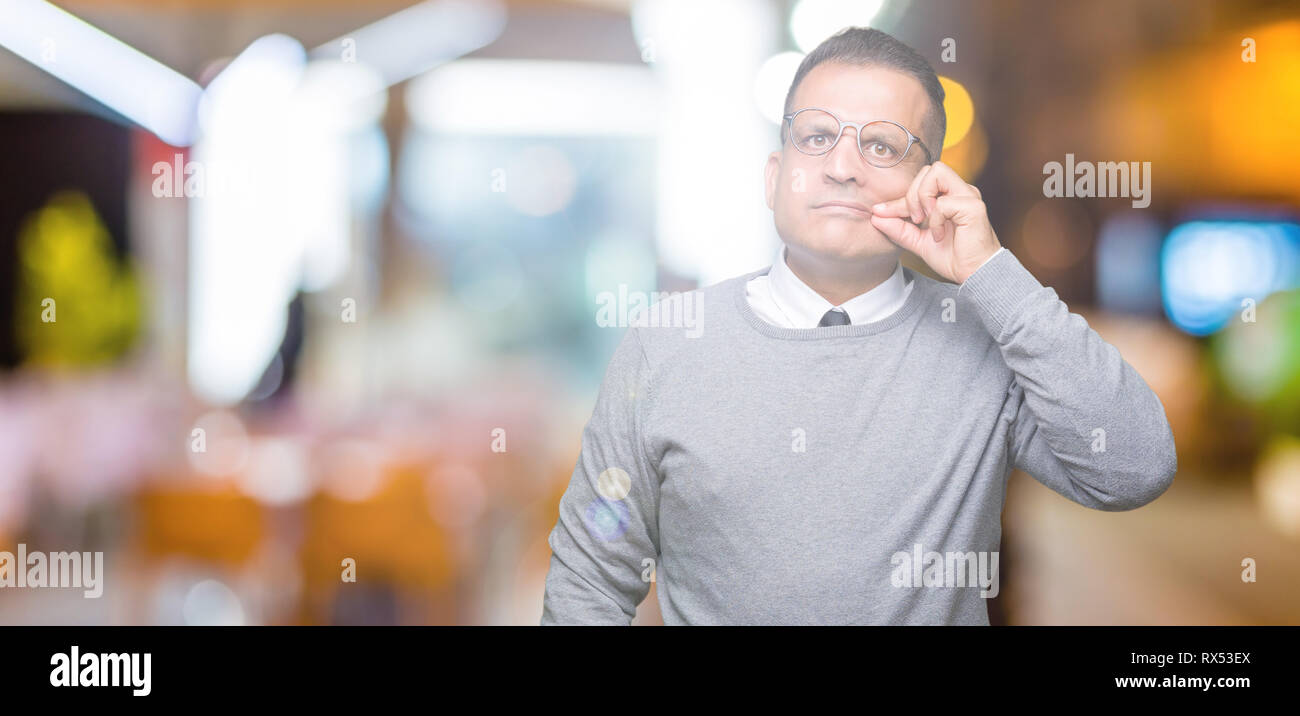 Middle age bussines arab man wearing glasses over isolated background mouth and lips shut as zip with fingers. Secret and silent, taboo talking - Stock Image