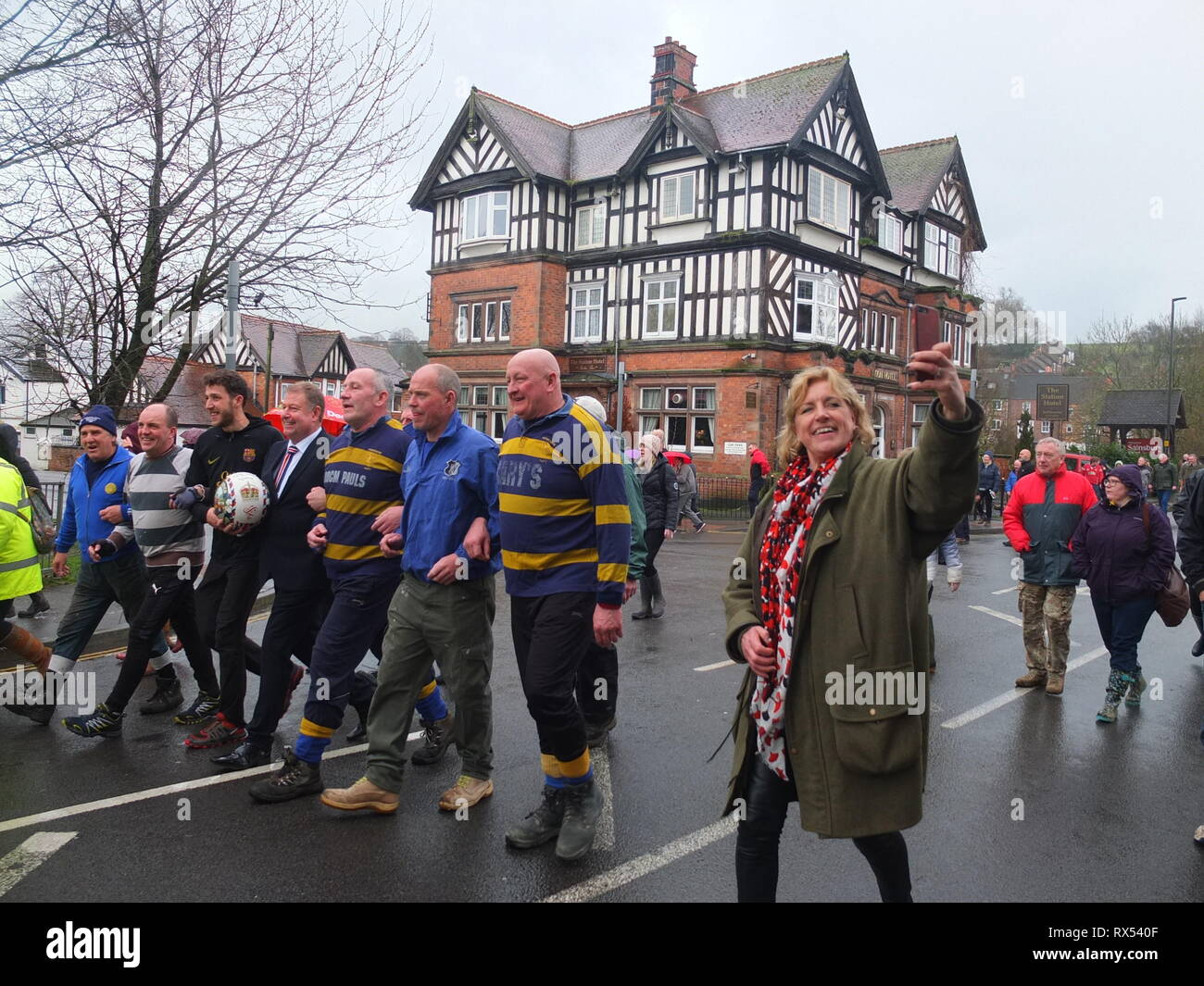 Ashbourne Shrovetide Football 2019. Local firefighter Paul Holmes is escorted through the town to turn up the ball for the Ash Wednesday Game. Stock Photo