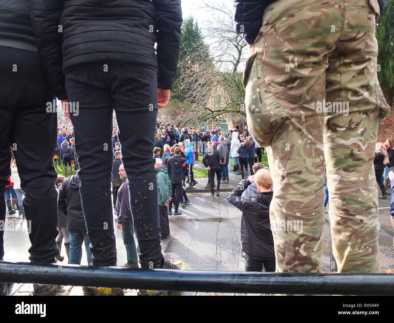 Ashbourne Shrovetide Football 2019. Players stand on wall trying to assess the direction the ball is moving in during the Ash Wednesday game. Stock Photo