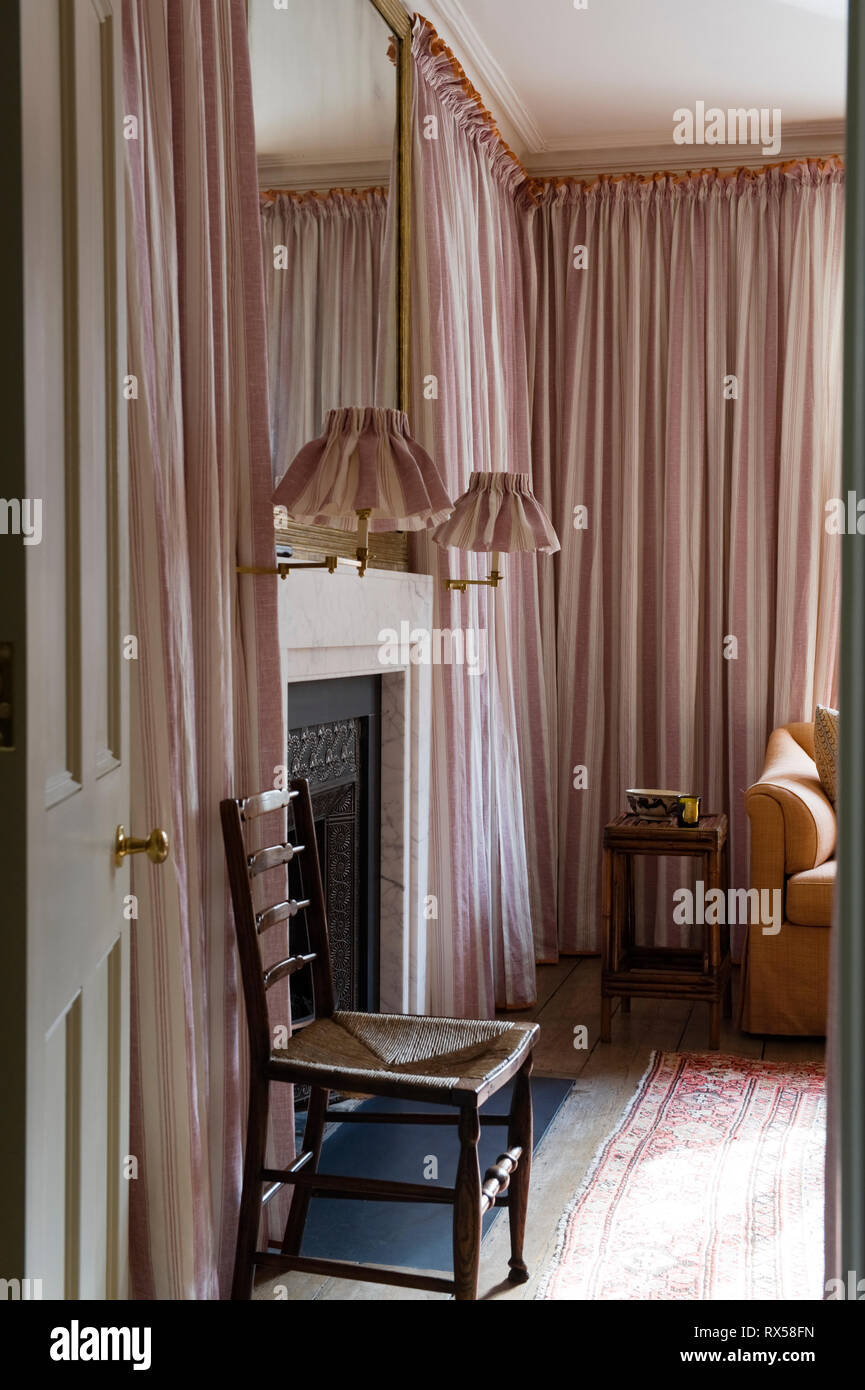 Fireplace in bedroom covered with pink curtains - Stock Image