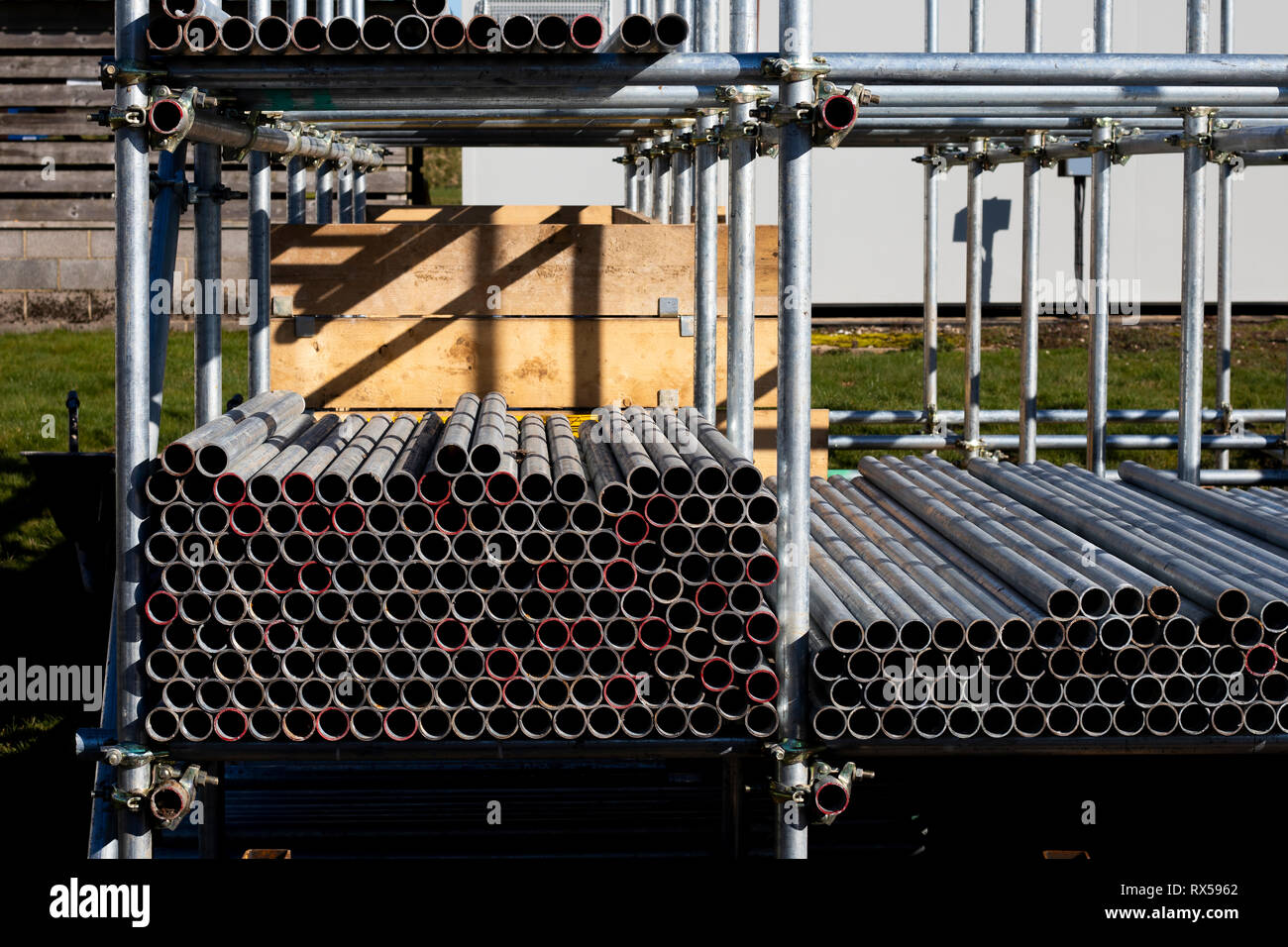 construction site scaffold storage area constructed using scaffolding poles - Stock Image