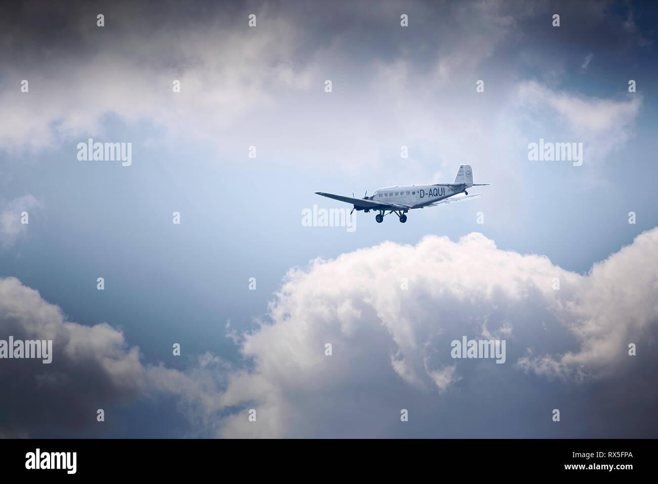 Tante Ju (Junker Ju 52) fliegt am dramatisch bewoelkten Himmel ueber Essen - Stock Image