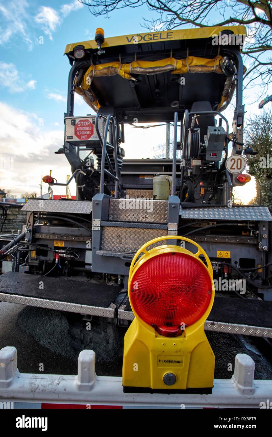 Ein Asphaltfertiger steht hinter einer Absperrung auf der ein rotes Lichtsignal montiert ist. - Stock Image