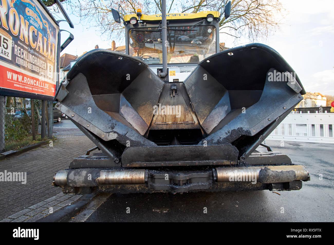 Ein Asphaltfertiger aus dem Strassenbau parkt an Strassenrand aus der Froschperspektive aufgenommen. - Stock Image