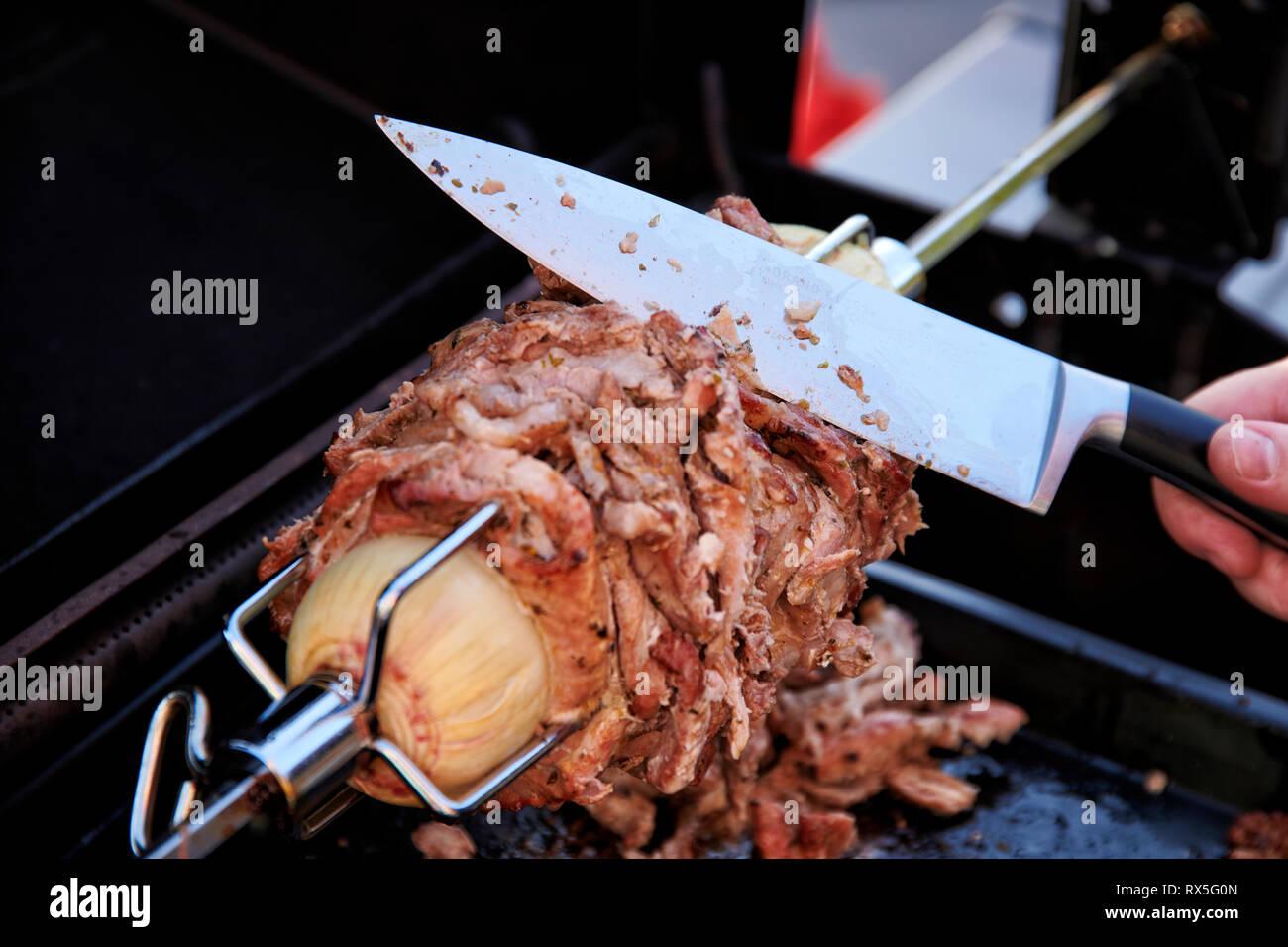 Von einem selbstgemachten Doenerspiess der in einem Grill eingespannt ist, wird mit einem grossen Messer eine Portion abgeschnitten. - Stock Image