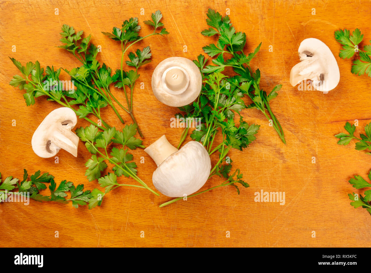 Champignons, whole and sliced, shot from the top on a rustic cutting board with fresh parsley leaves and a place for text - Stock Image