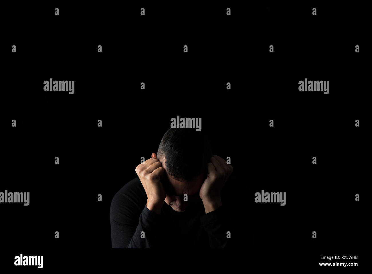 closeup of a desperate young caucasian man with his hands in his head, against a black background, with some blank copy space around him - Stock Image