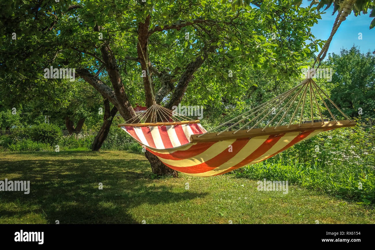 A striped hammock between two trees in a sunny green garden. Concept for holidays, summer vacation and lazy days. - Stock Image