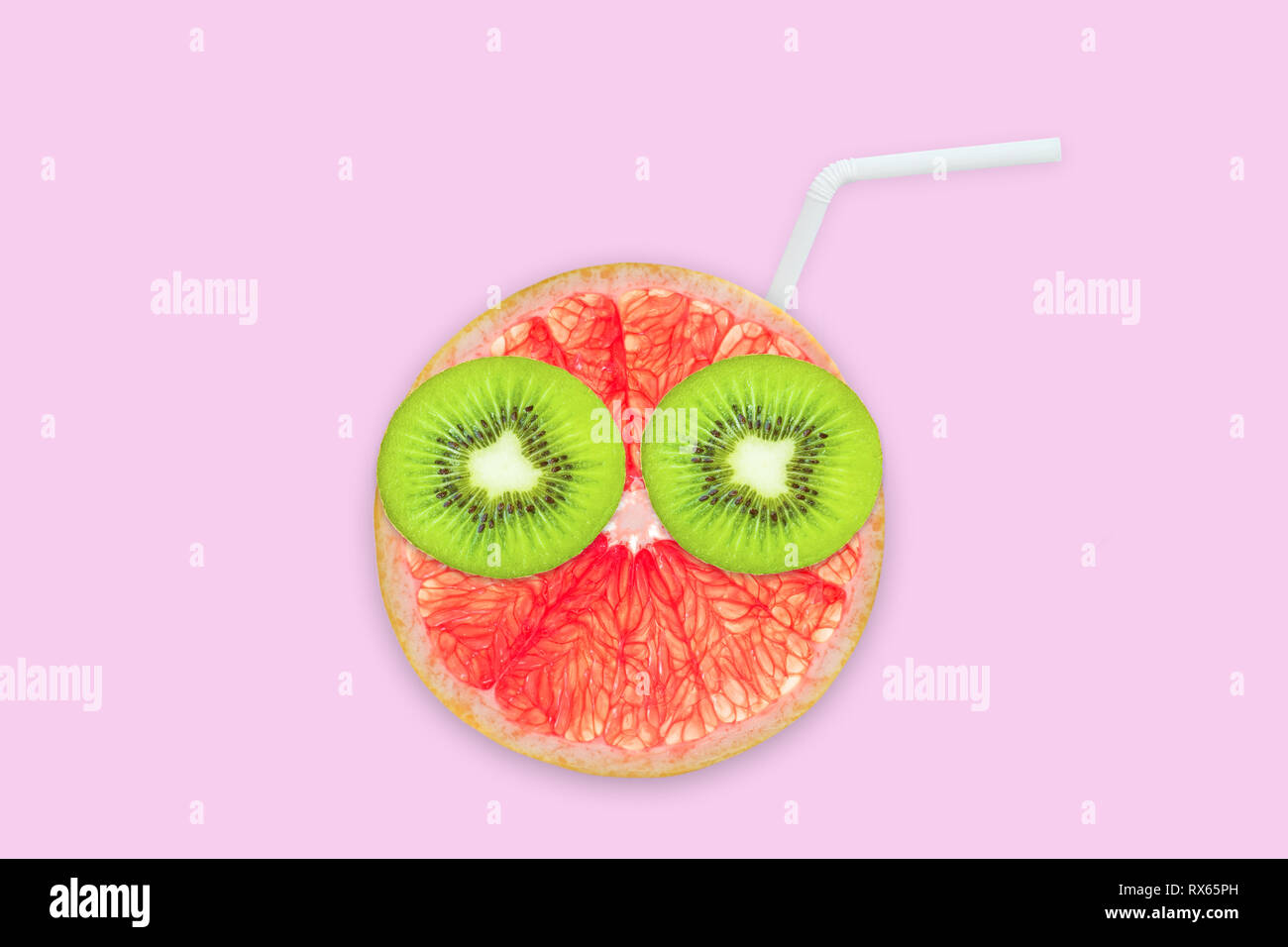 Fruit creative face with slices of grapefruit and kiwi, drinking straw on pink background, fruit juice and summer concept - Stock Image