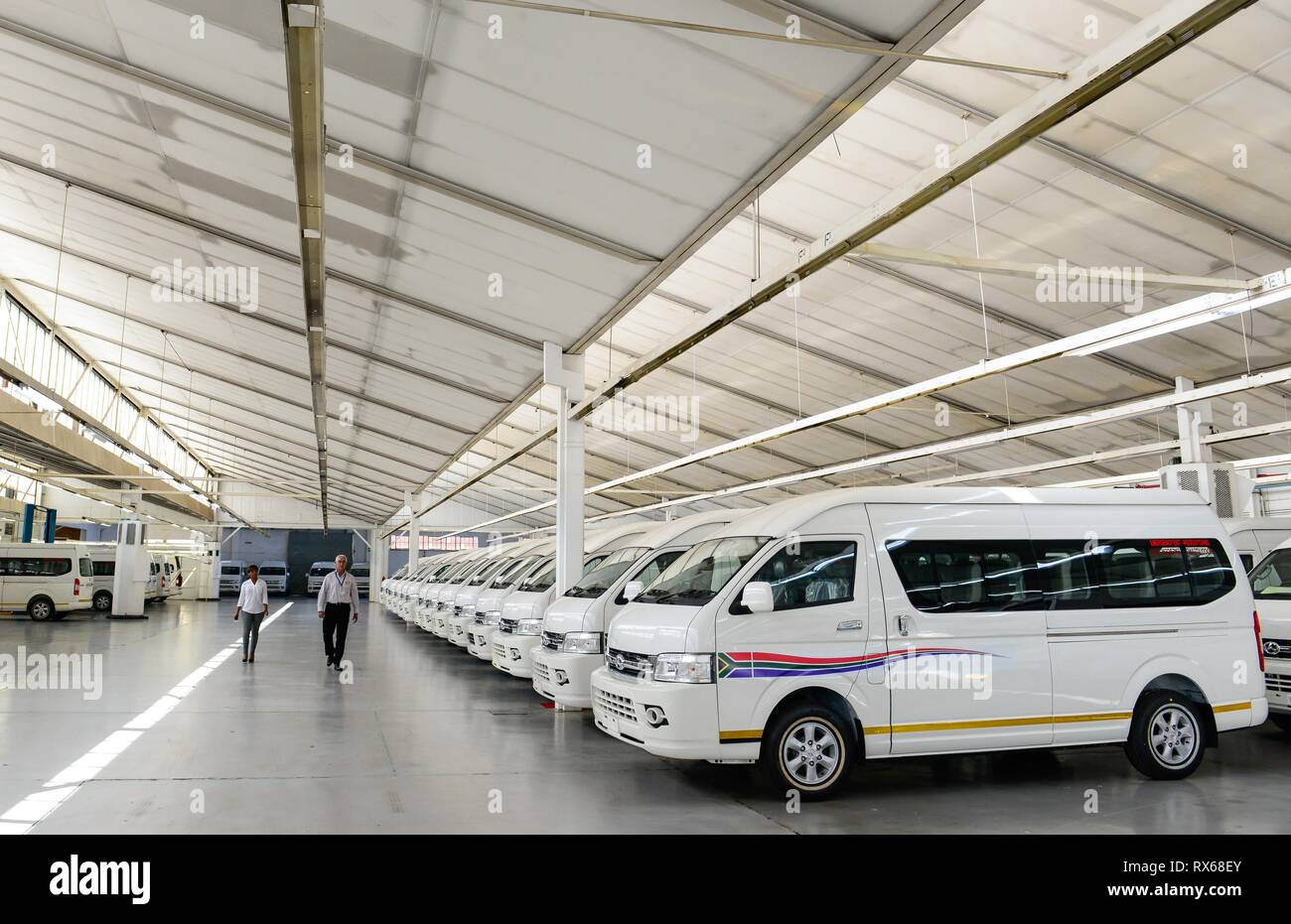 Beijing, Johannesburg, China. 19th Apr, 2016. Two staff members walk past buses at the automobile plant of Beijing Automobile Works Co., Ltd (BAW), known as BAW South Africa in Springs, west of Johannesburg, on April 19, 2016. Credit: Zhai Jianlan/Xinhua/Alamy Live News - Stock Image