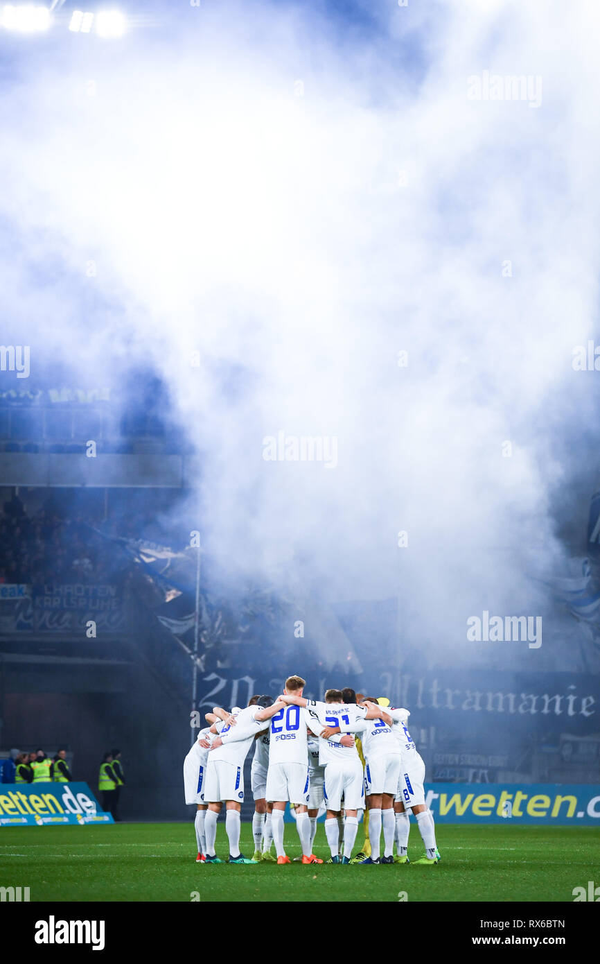 The Karlsruhe team together in a circle. Behind them are the Karlsruhe fans Pyro. GES / football / 3rd league: Krefelder football club Uerdingen - Karlsruher SC, 08.03.2019 Football / Soccer: 3rd League: KFC Uerdingen vs Karlsruher SC, Duisburg, March 8, 2019 | usage worldwide - Stock Image