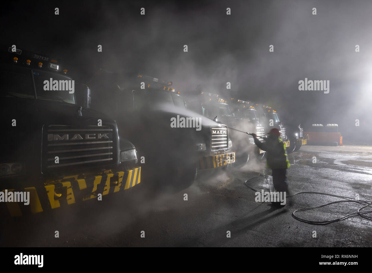 Worker spray washing construction dump trucks very early in the morning - Stock Image