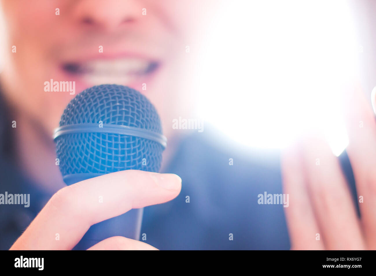 Young man holding a black microphone and speaking into it - Stock Image