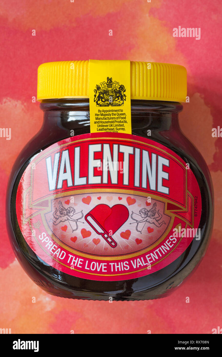 Special edition jar of Valentine Marmite by Unilever - spread the love this Valentines set on red patterned background - Stock Image