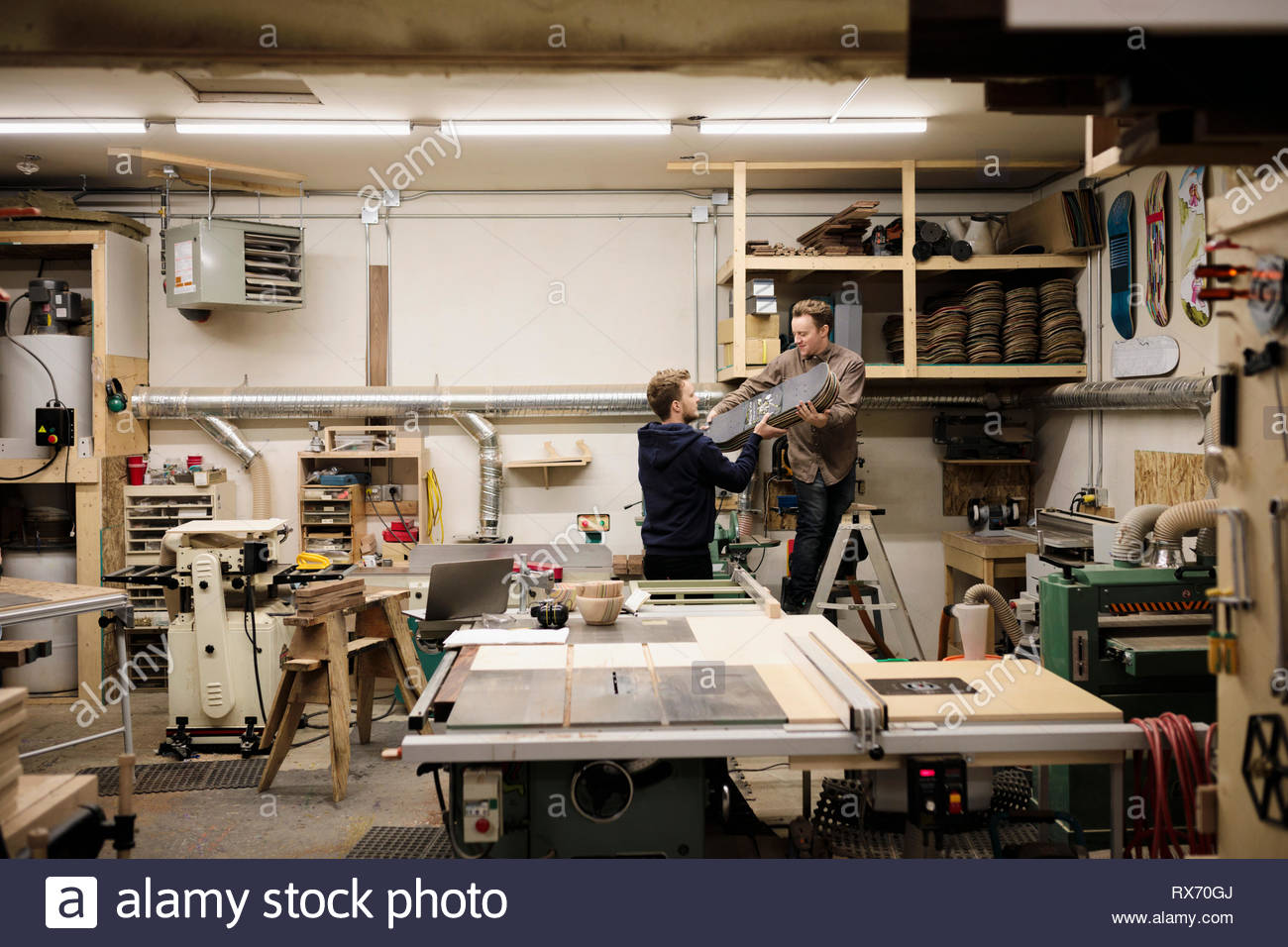Creative artists using recycled skateboards in woodworking workshop - Stock Image