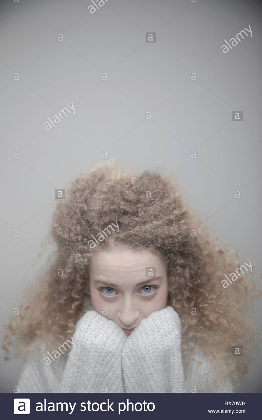 Portrait confident beautiful young woman with curly blonde hair - Stock Image