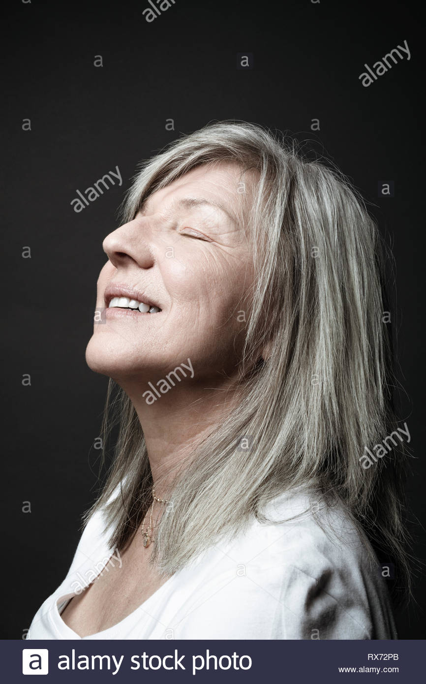 Portrait serene beautiful senior woman with gray hair and eyes closed with head back - Stock Image