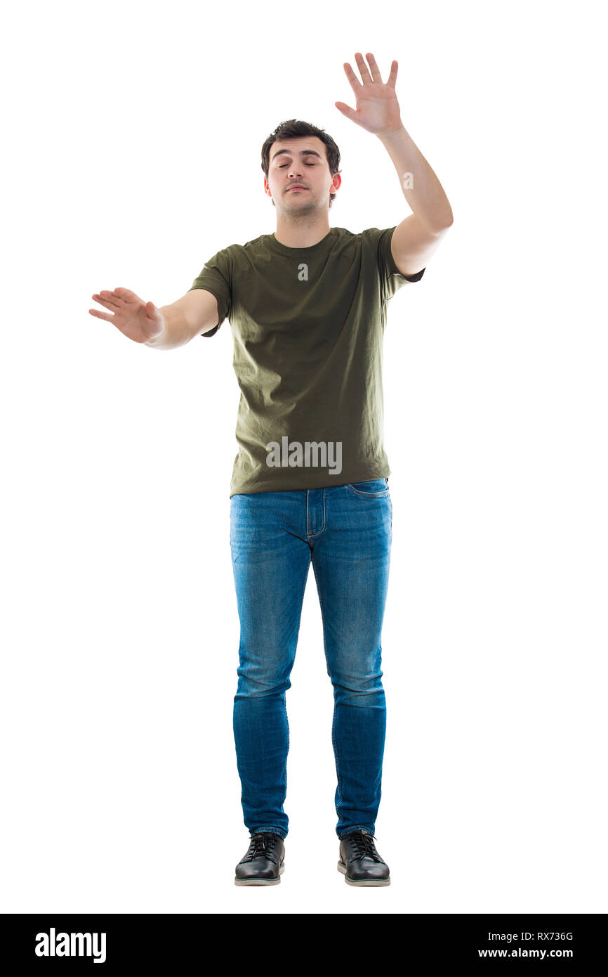 Full length portrait casual young man searching with hands outstretched and eyes closed like blind walking in the darkness isolated over white backgro - Stock Image