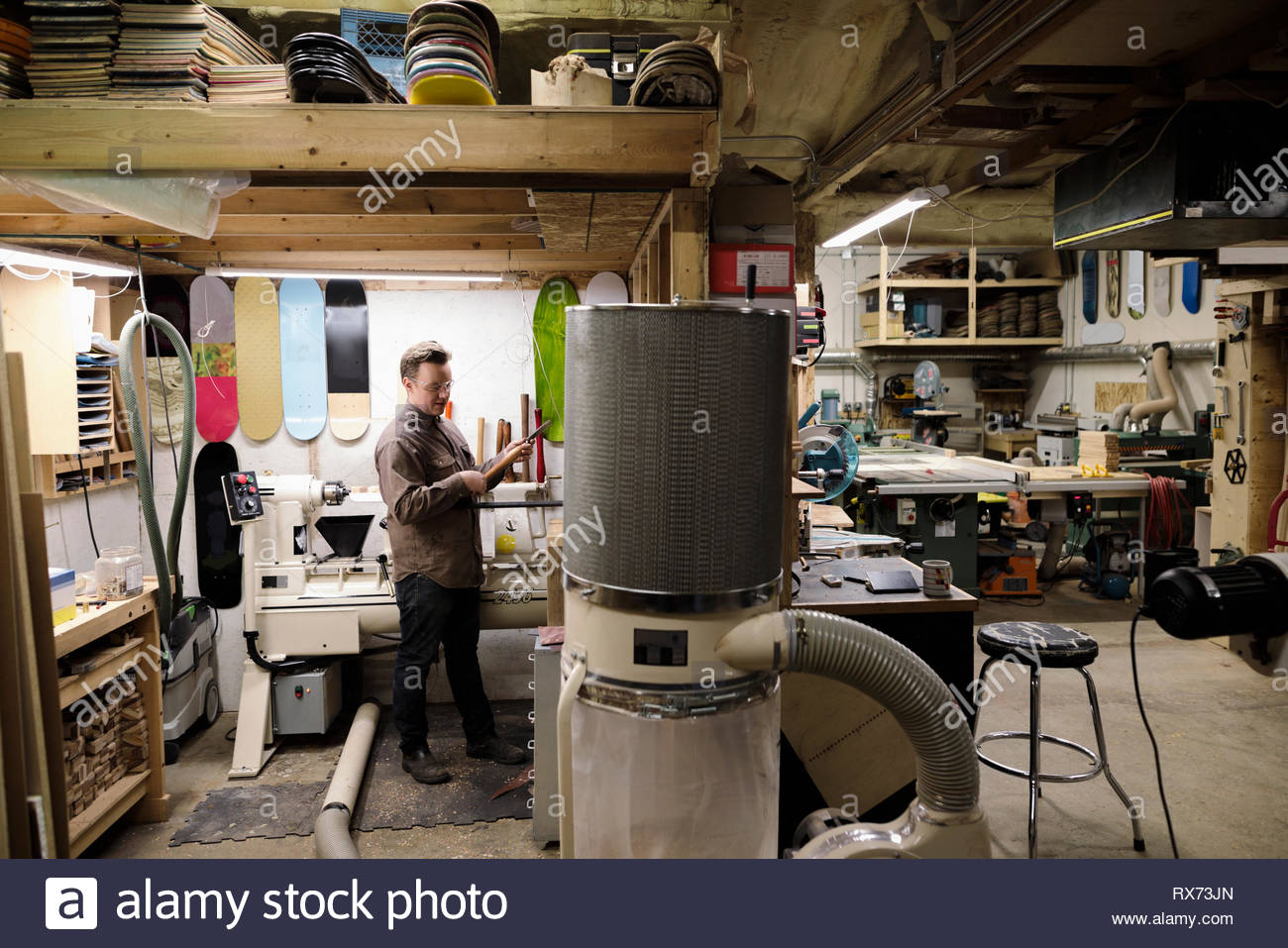 Male artist working with recycled skateboards in workshop - Stock Image