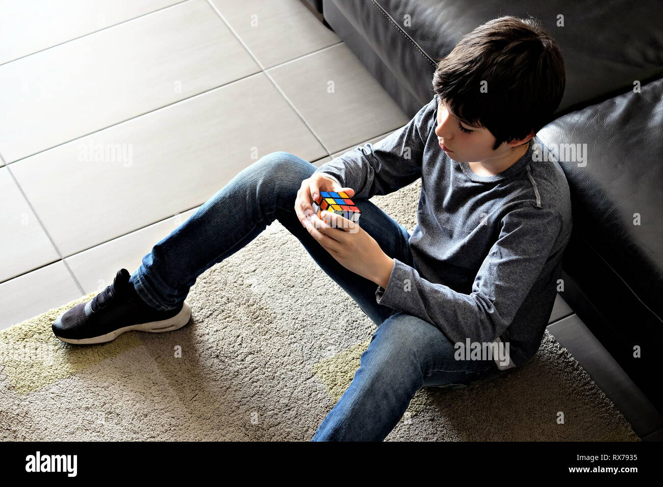 kid enjoying Rubik's cube - Stock Image