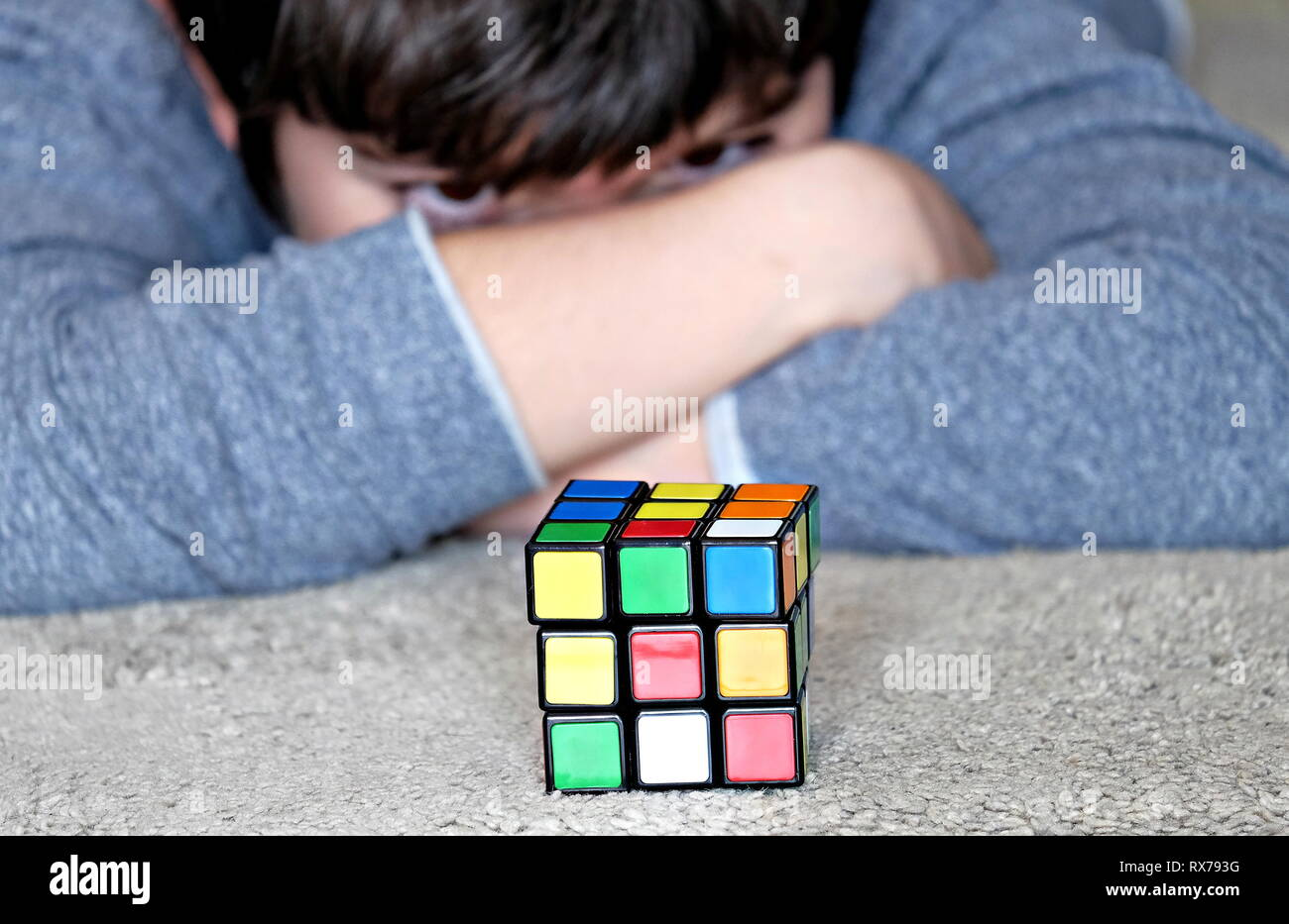 kid enjoying Rubik's cube, searching a solution - Stock Image