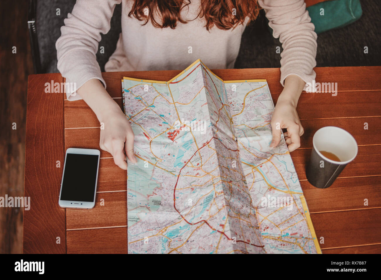 Young woman red head girl traveller reading looking at paper map in cafe - Stock Image