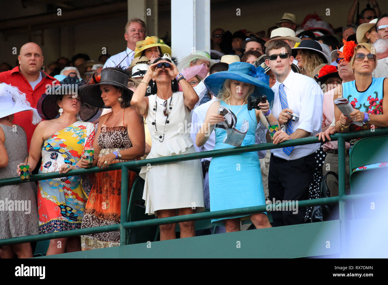 Kentucky Derby Horse Race at Louisville, USA - Attendants of the Derby dressed with fancy clothes observe the horse races from the stands - Stock Image
