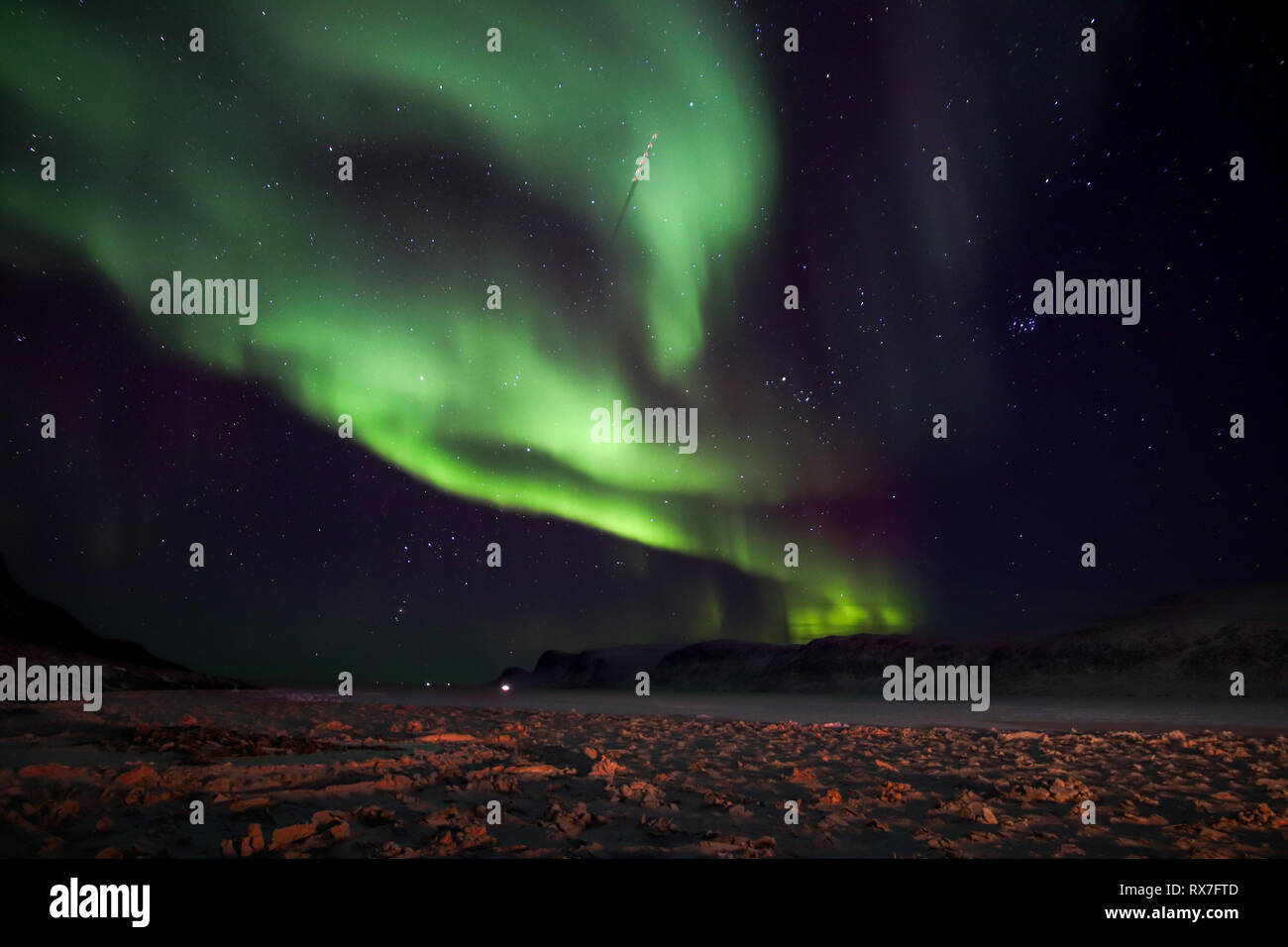 Aurora Borealis viewed from the small Arctic town of Pangnirtung over the frozen Cumberland Sound. - Stock Image