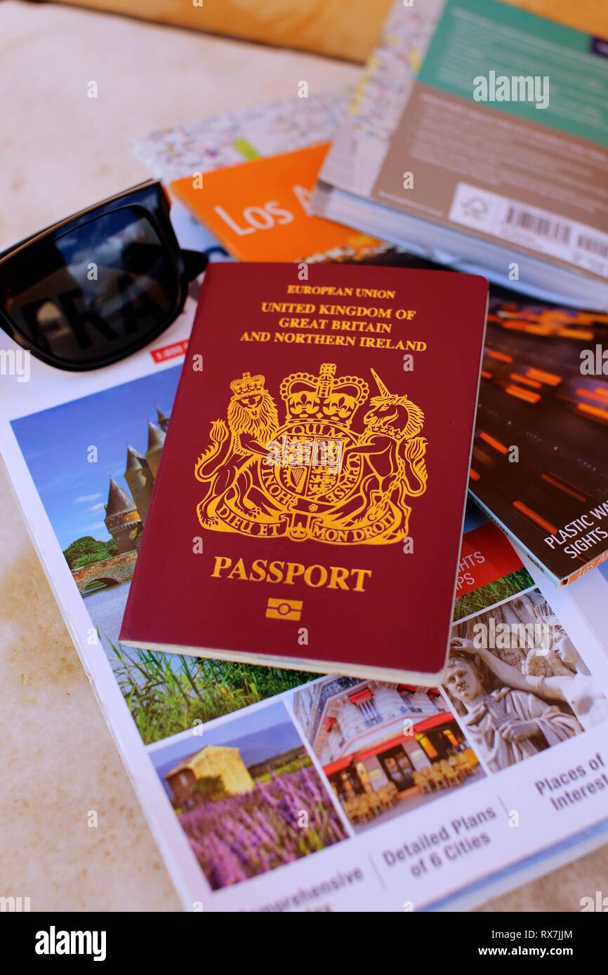 Close up of UK passport with maps, travel guides and sunglasses - Stock Image