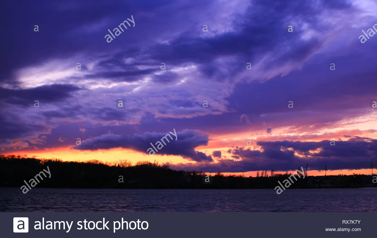 Cumulonimbus very dark above the sea in the evening. Stormy sky at sunset with many flaming colors - Stock Image