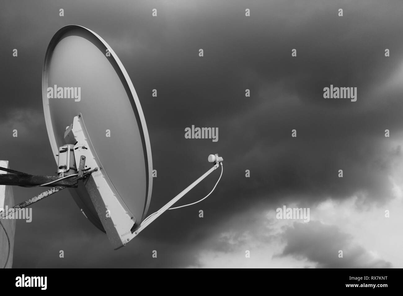 Black and white satellite dish on a rooftop against a cloudy moody sky background - Stock Image