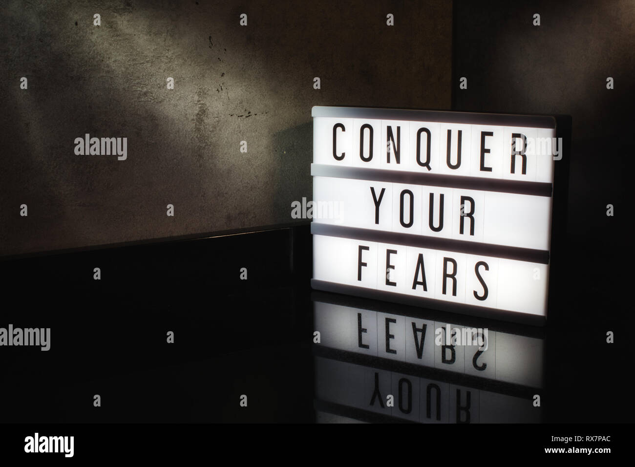 Conquer your fears motivational message on a light box in a cinematic moody background - Stock Image