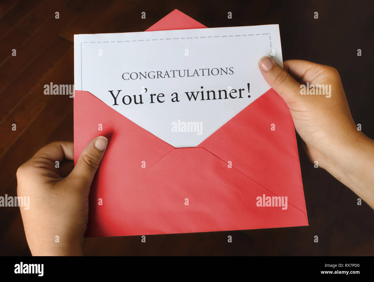An open red envelope with a letter that says Congratulations You're a winner! with female hands holding it up - Stock Image