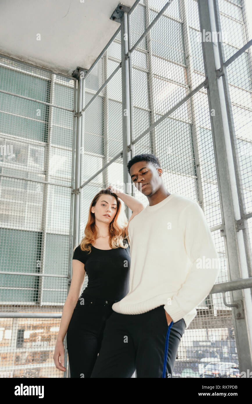 A good looking couple are standing in front of a modernist tower block in a city. She is white he is black, they are serious Stock Photo