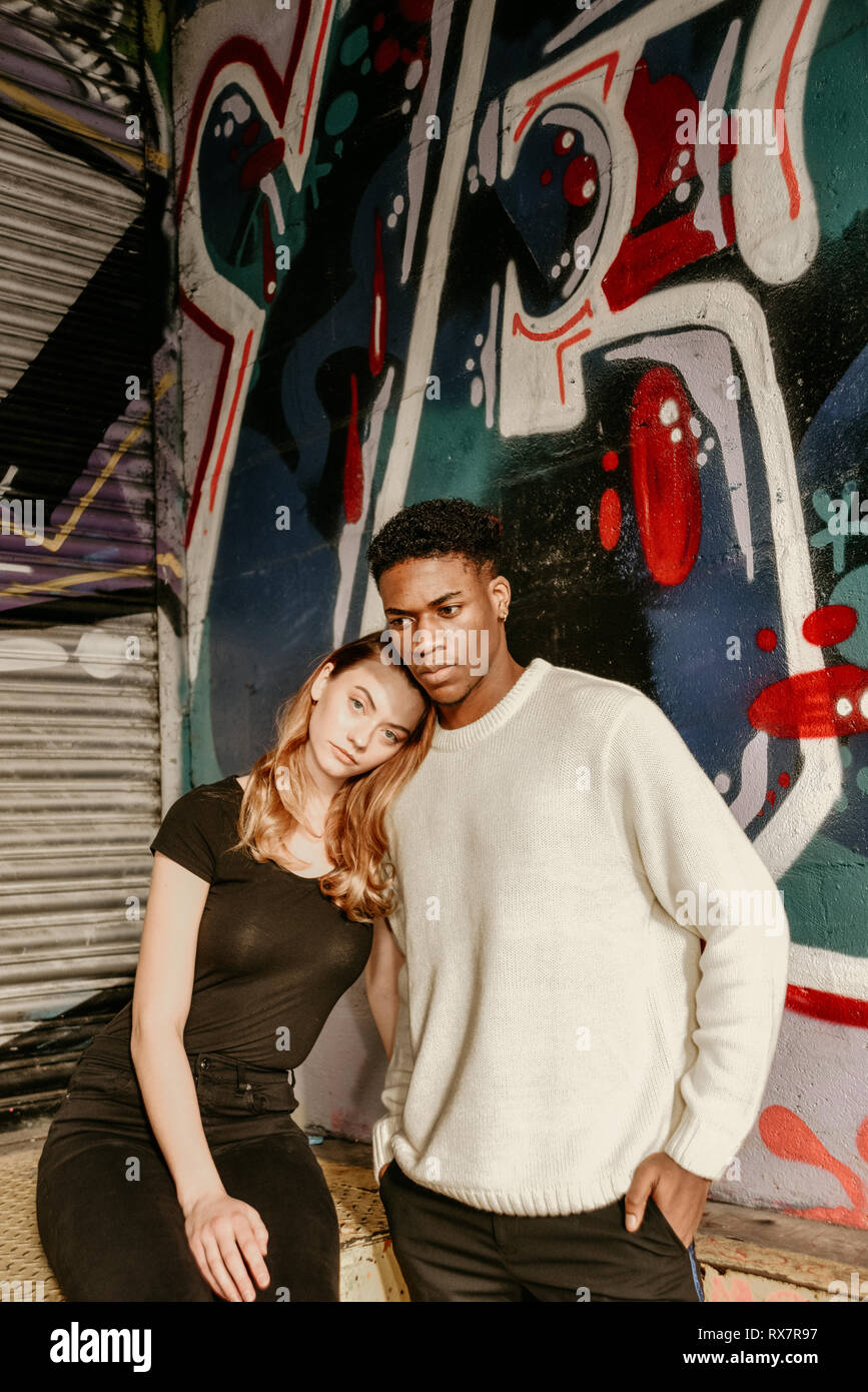 A good looking couple are standing in front of a Graffiti wall in an urban location. She is white, he is black. They are serious Stock Photo