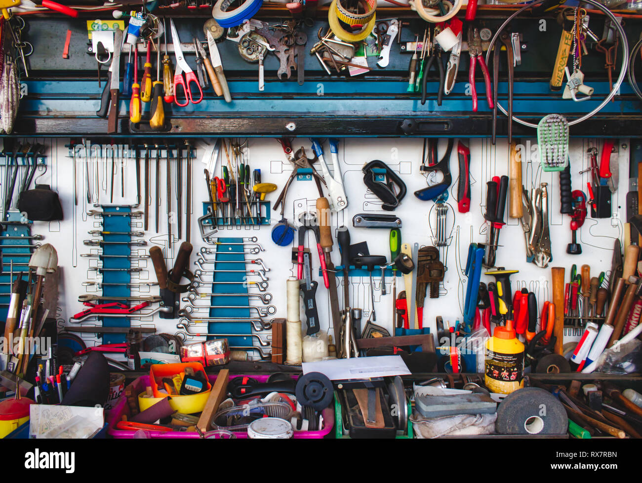 A collection of assorted tools hanging on the wall with a work bench in a garage - Stock Image