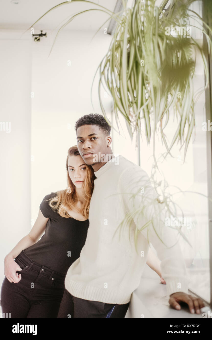 A good looking and young couple poses with next to each other and look at the camera. She is White, he is black  They have serious faces Stock Photo