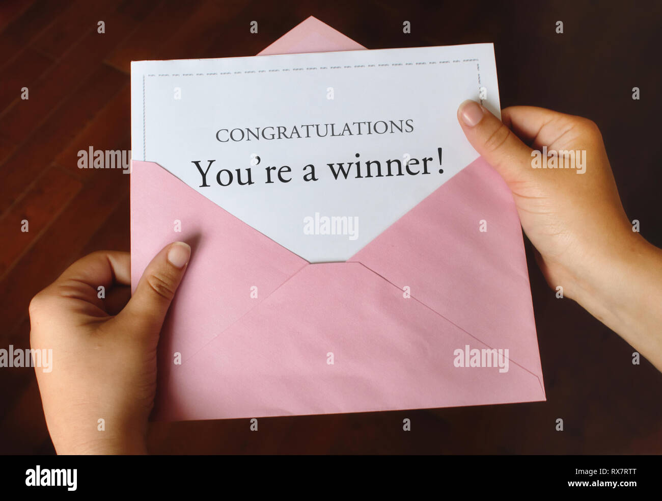 A letter that says Congratulations You're a winner! with female hands holding the open pink envelope - Stock Image