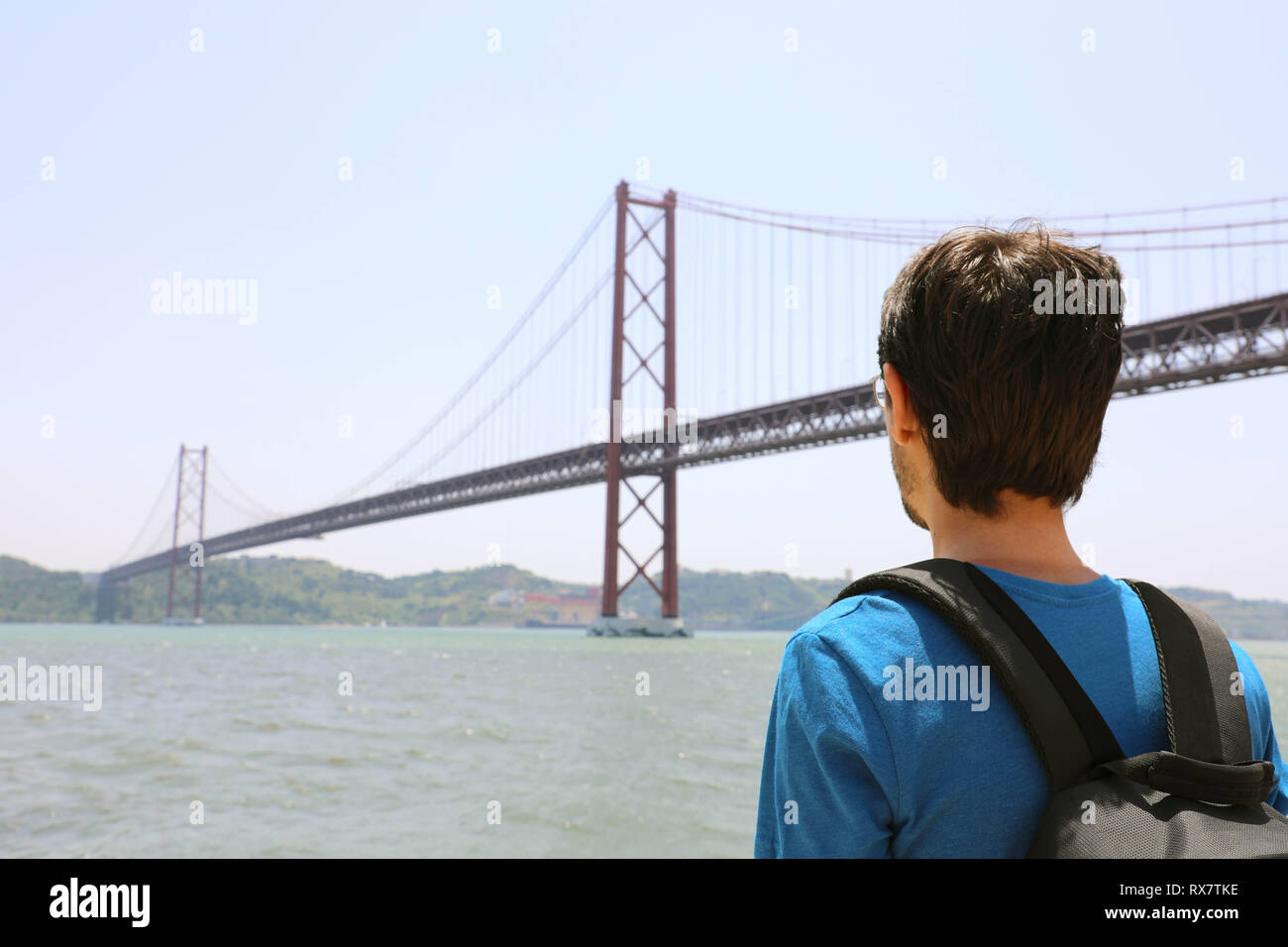 Back view of young backpacker man looking at bridge. Traveler or tourist with backpack on the waterfront in Lisbon Portugal next to the 25th of April  - Stock Image