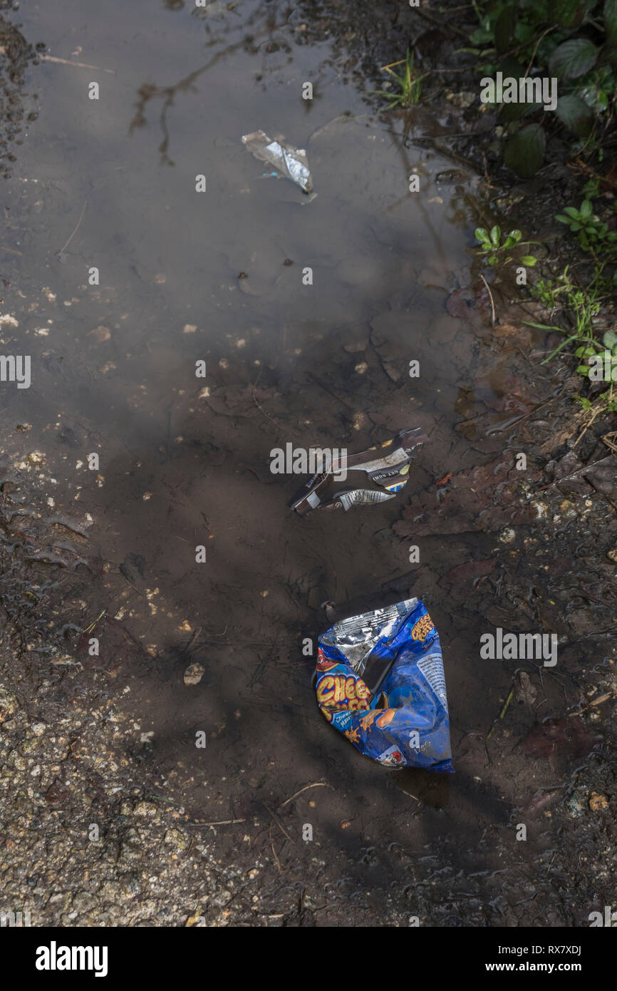 Discarded plastic food packaging on a rural countryside footpath in UK. Stock Photo