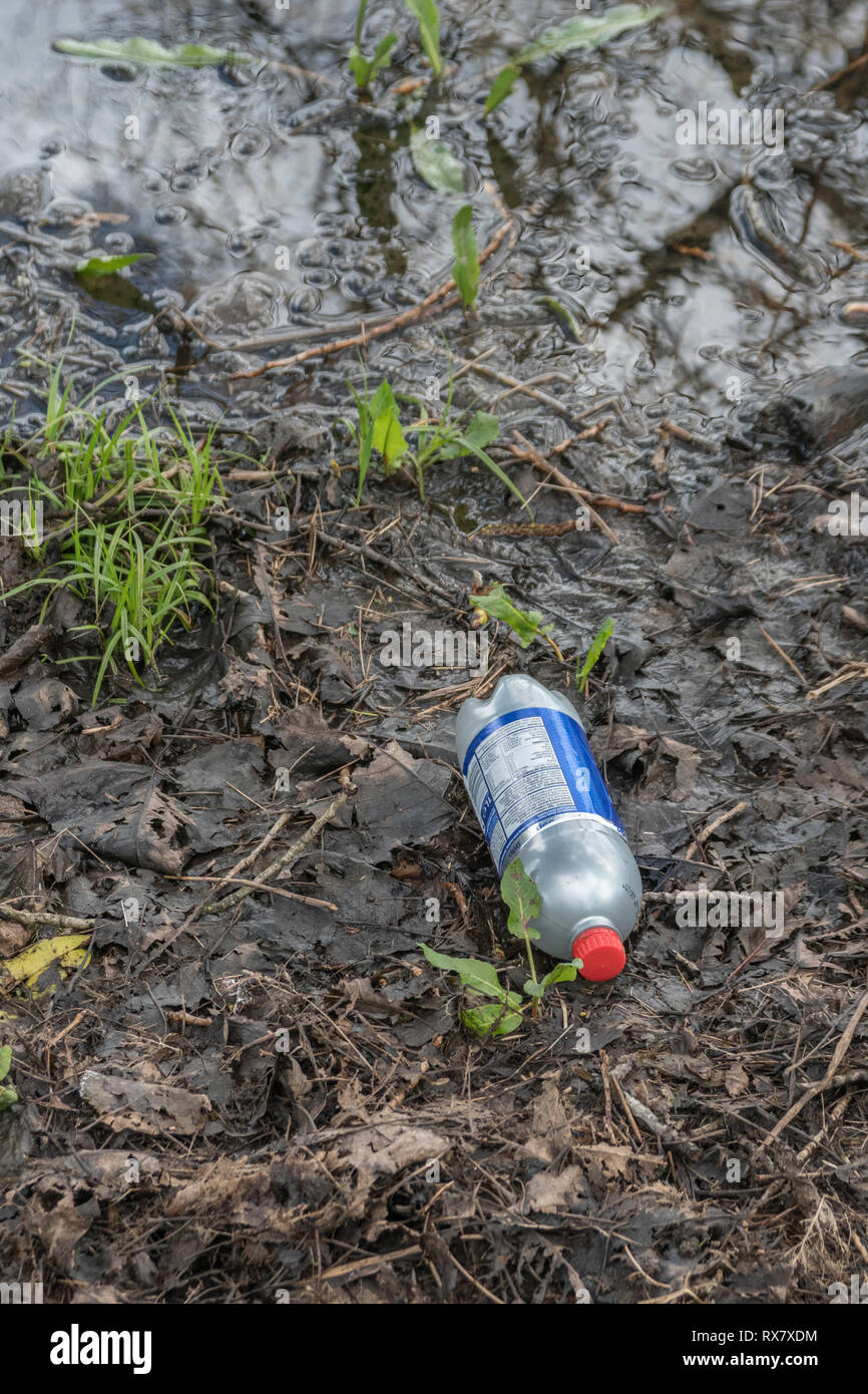 Discarded plastic soft drinks bottle in a corner of a wet field in the UK countryside. - Stock Image