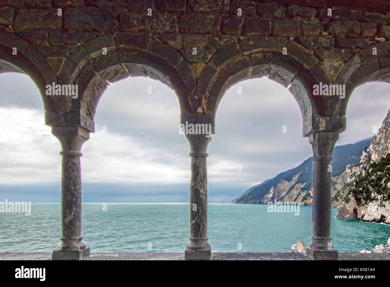 Landscape of gulf of poets at Porto Venere framed by gothic columns of Saint peter's porch in Liguria, Italy - Stock Image